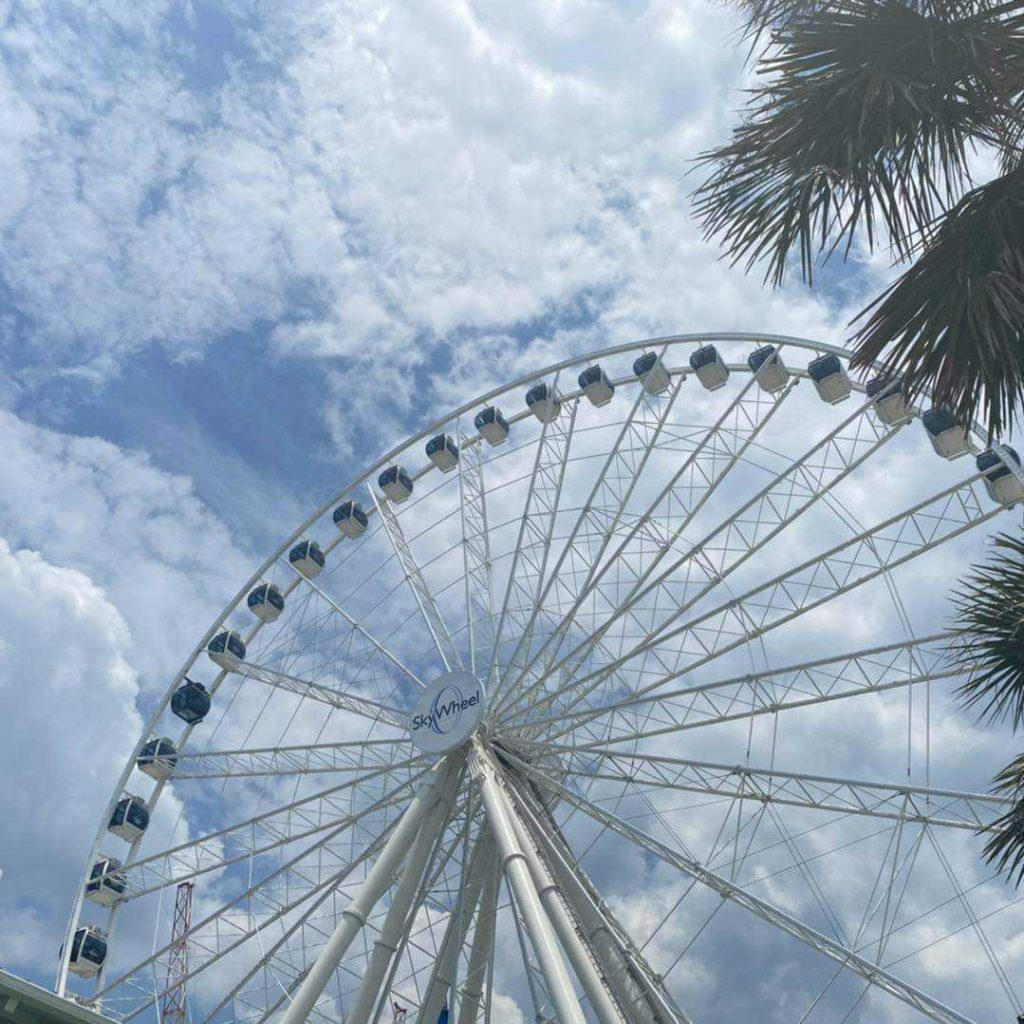 Picture of Myrtle Beach Skywheel showing during the day with gondolas and clouds in the sk