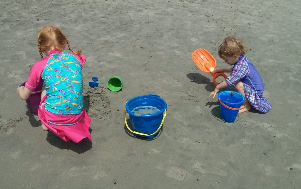 two young girls with red hair playing in sand at beach with pails, sand, shovels and water in swimsuits